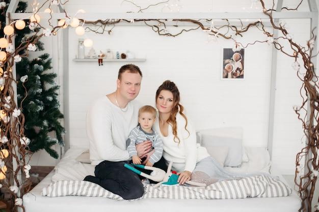 Mãe e pai encantadores com o filho pequeno e fofo, deitados juntos na cama, olhando para a frente e posando no estúdio no inverno