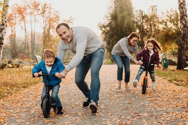 Mãe e pai ensinando seus filhos a andar de bicicleta no parque.