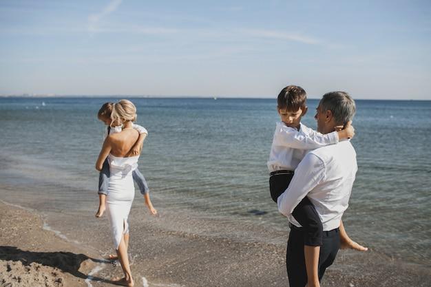 Mãe e pai estão segurando filhos jovens nas mãos no dia ensolarado de verão, caminhando à beira-mar