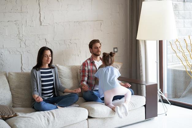 Mãe e pai exaustos, sentados no sofá, sentem-se cansados e irritados, enquanto a filhinha barulhenta grita e corre ao redor do sofá.