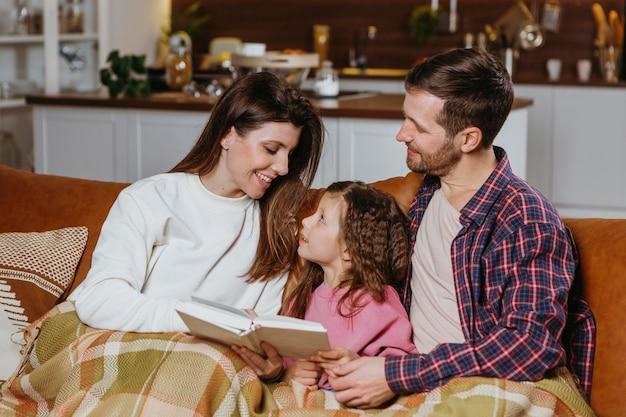 Mãe e pai lendo livro com a filha em casa