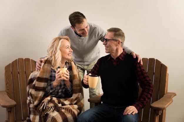 Mãe e pai posando com o filho, segurando copos