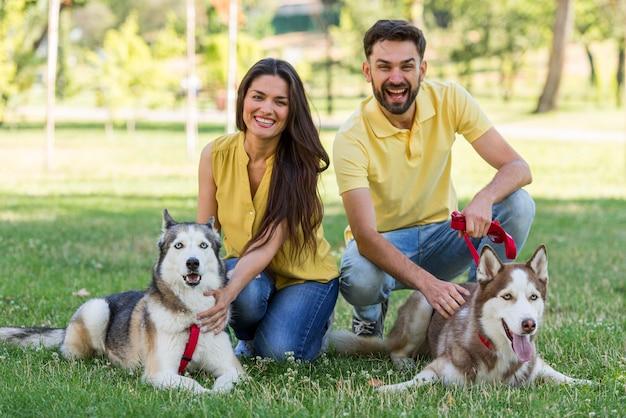 Mãe e pai posando com seus cachorros no parque