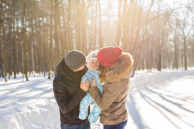 Mãe e pai segurando seu filho e beijando-o do lado de fora no inverno.