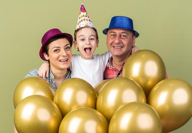 Mãe e pai sorridentes usando chapéus de festa em pé com o filho e segurando balões de hélio isolados na parede verde oliva com espaço de cópia