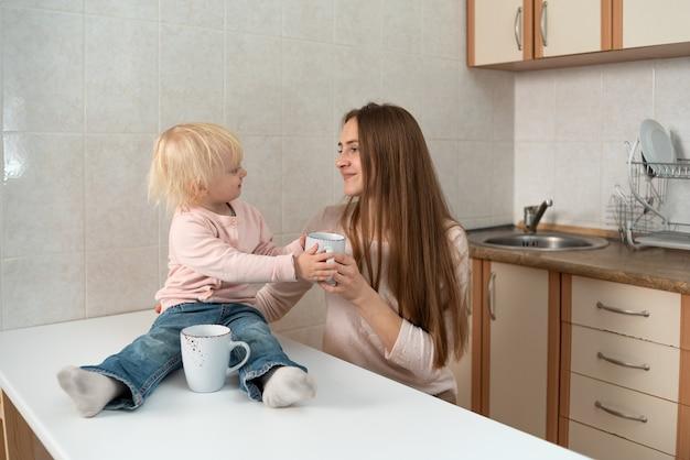 Mãe e pequena comunicação linda garota na cozinha. manhã em família.
