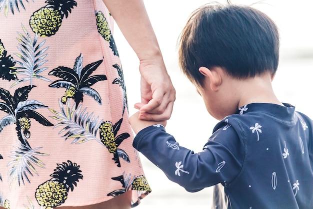 Mãe e rapaz pequeno que guardam as mãos que estão na praia. amor do conceito de família