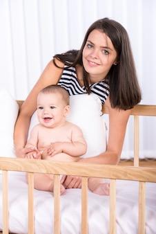 Mãe e seu bebezinho no berço em casa.