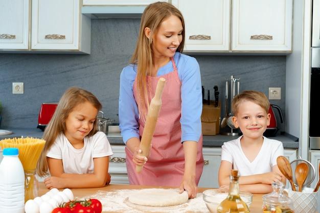 Mãe e seus filhos, menino e menina, ajudando-a a preparar a massa