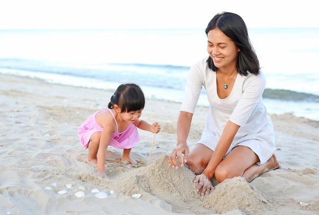 Mãe e sua filha criança menina jogando areia na praia