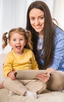 Mãe e sua filha estão olhando para tablet.