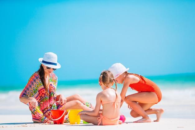 Mãe e suas filhas fazendo um castelo de areia