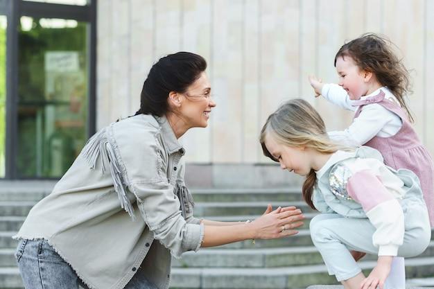 Mãe e suas filhas fofas em uma rua