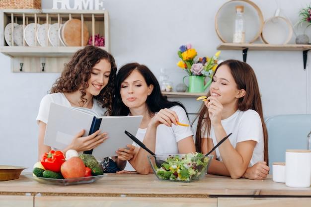 Mãe e suas lindas filhas lendo uma receita deliciosa de jantar e preparando uma salada útil na cozinha