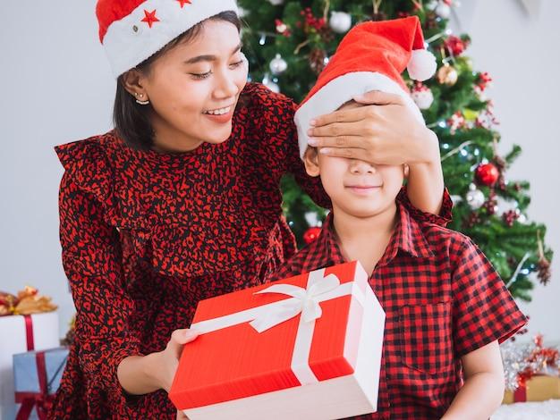 Mãe é surpreendida filho fechando os olhos com caixa de presente
