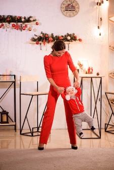 Mãe elegante, brincando com o menino com chapéu de papai noel, sentada no chão perto de decorações de natal