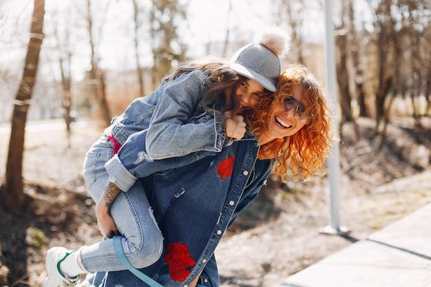 Mãe elegante com a filha em um parque de verão
