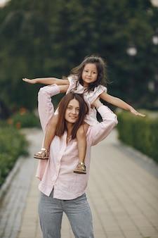 Mãe elegante com filha em um parque de verão