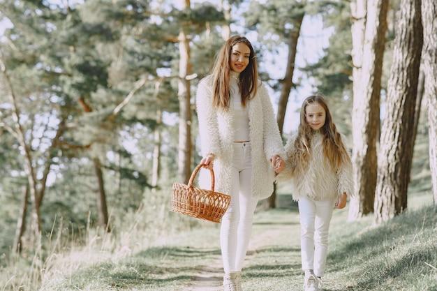 Mãe elegante com filha em uma floresta de verão