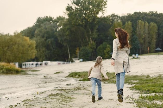 Mãe elegante com filha. pessoas caminham fora