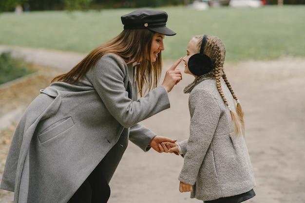 Mãe elegante com filha. pessoas caminham lá fora. mulher com um casaco cinza.