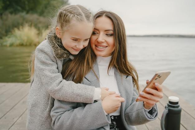 Mãe elegante com filha. pessoas em um piquenique. mulher com um casaco cinza. família perto da água.