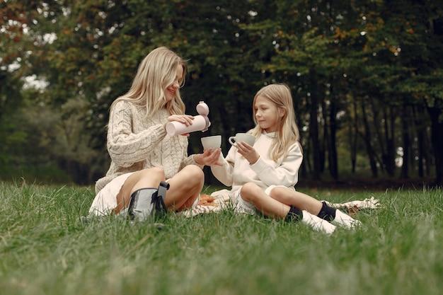 Mãe elegante com filha. pessoas sentadas na grama
