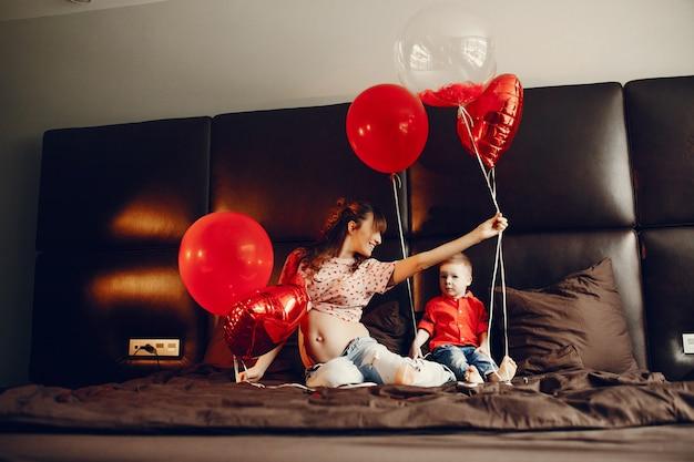 Mãe elegante com filho pequeno em uma cama