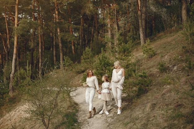 Mãe elegante com filhos em uma floresta de verão