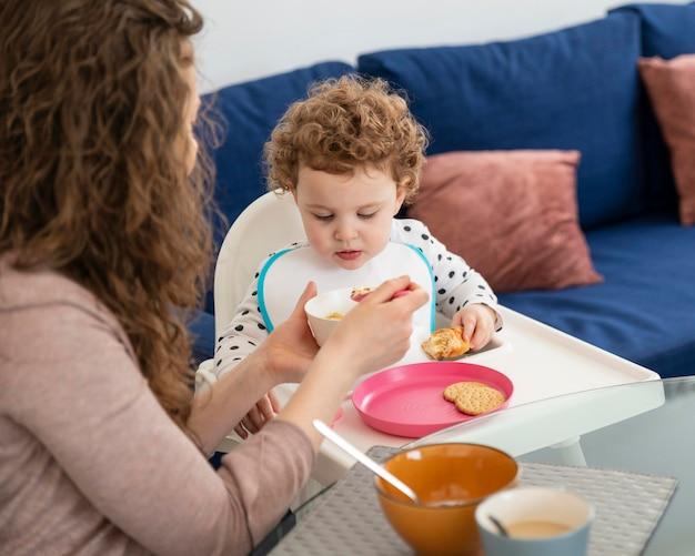 Mãe em casa com filho almoçando
