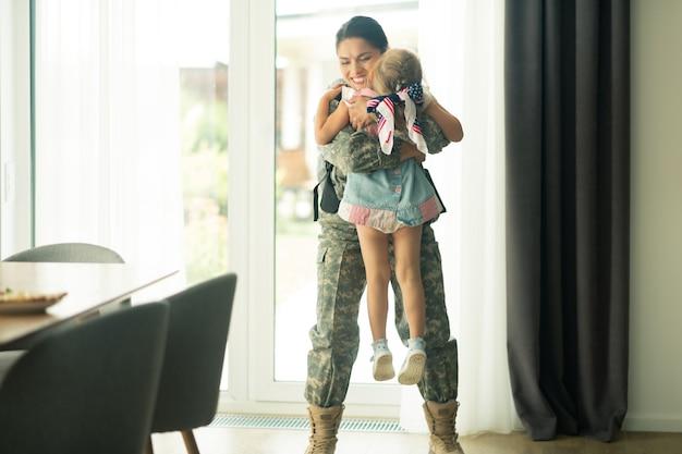 Mãe em casa. mulher vestindo uniforme militar levantando sua filha enquanto voltava para casa