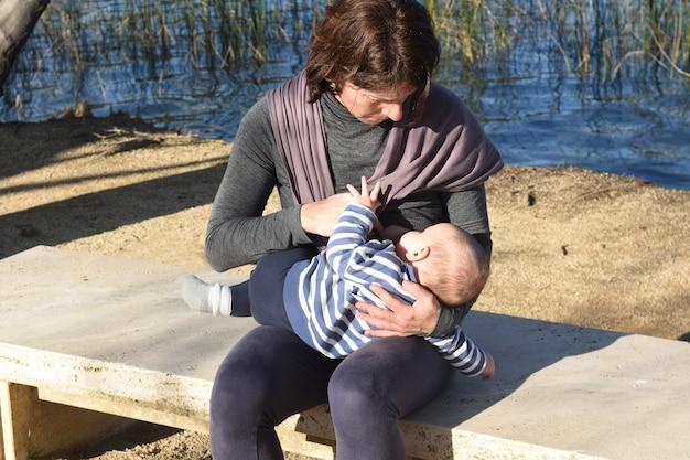 Mãe em roupas esportivas amamentando seu filho