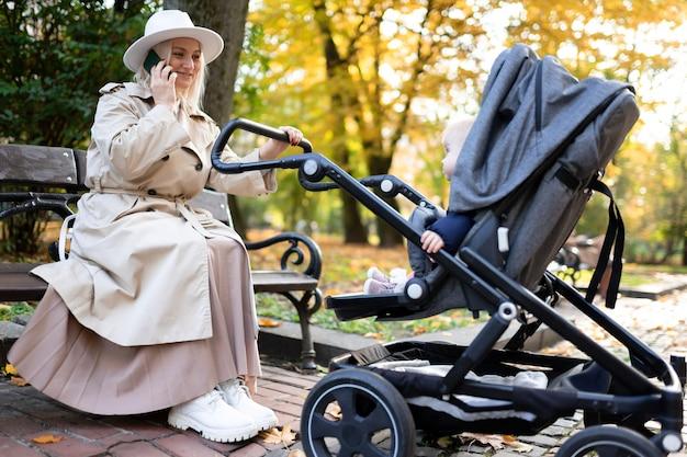 Mãe embalando bebê recém-nascido no carrinho e falando ao telefone