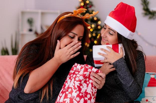 Mãe empolgada com bandana de rena olha para a sacola de presentes e filha satisfeita com chapéu de papai noel abraça sua caixa de presente sentada no sofá, aproveitando o natal em casa
