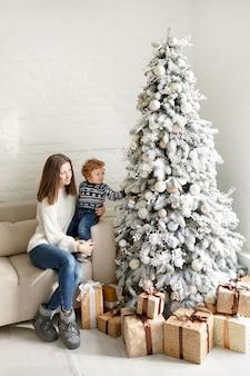 Mãe encantadora com o suéter branco segurando seu filho pequeno perto da árvore de natal e caixas de presente na sala de estar da casa