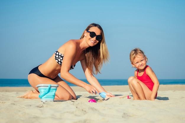 Mãe encantadora e filha brincando na areia e construindo um castelo de areia na praia.
