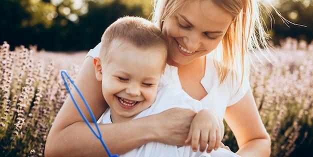 Mãe encantadora e filho sorrindo e se abraçando em um campo de lavanda fazendo balões com um brinquedo especial