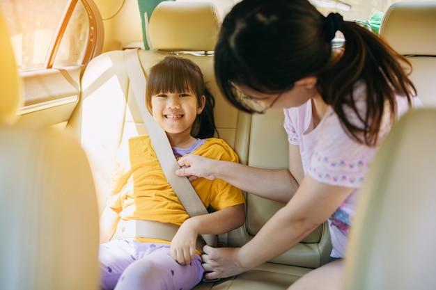 Mãe ensina a criança a usar o cinto de segurança normal no carro quando ela tiver entre 8 e 12 anos de idade