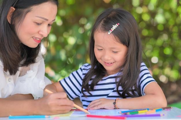 Mãe ensina filha a crianças asiáticas fazendo lição de casa na horta ou parque