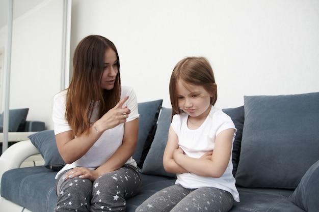 Mãe ensina filha. mãe repreende menina. a pequena garota está ofendida