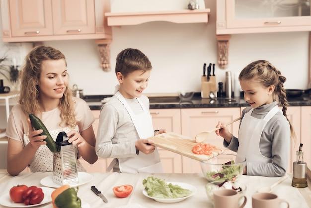Mãe ensina menino e menina cozinhar salada caseira.