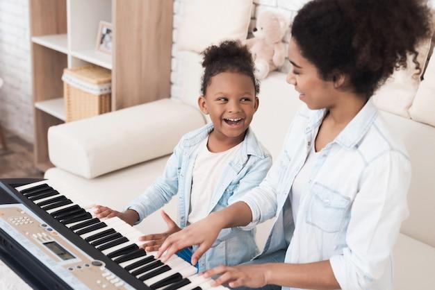 Mãe ensina uma menina a tocar piano.