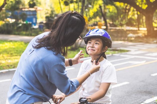 Mãe ensinando a filha a andar de bicicleta no parque. família ao ar livre em um passeio de bicicleta.