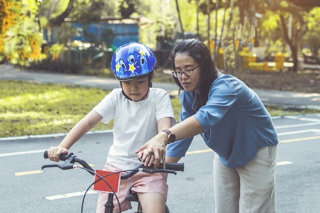 Mãe ensinando a filha a andar de bicicleta no parque