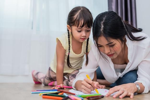 Mãe ensinando a filha a desenhar na aula de arte. de volta à escola e conceito de educação