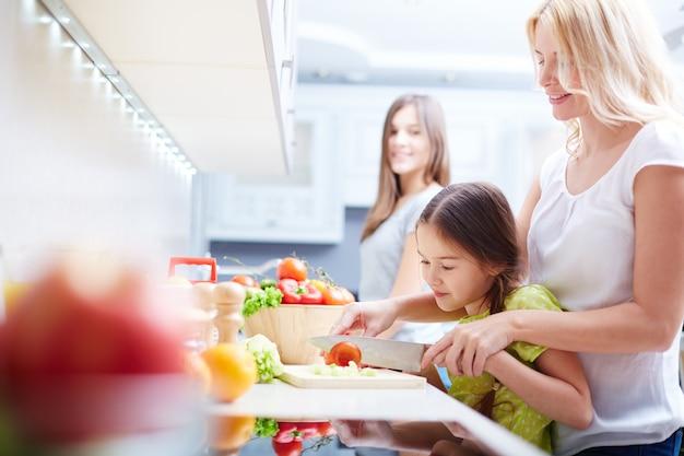 Mãe ensinando a sua filha como cozinhar