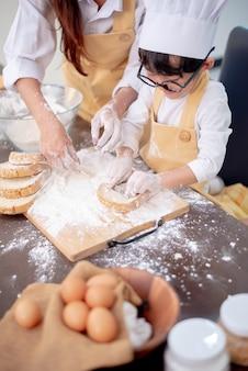 Mãe ensinando criança a cozinhar comida. preparar um ingrediente com pó e pão.