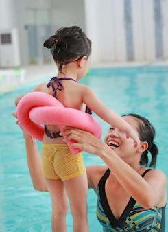 Mãe, ensinando, criança, em, piscina, com, macarronada espuma