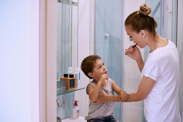 Mãe ensinando criança escovar os dentes