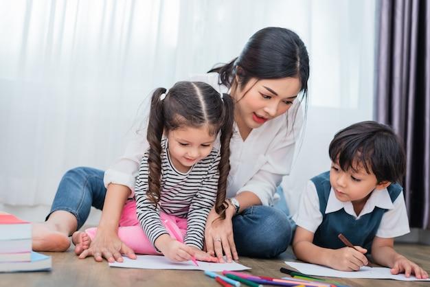 Mãe ensinando crianças na aula de desenho. filha e filho pintando com cor de creiom